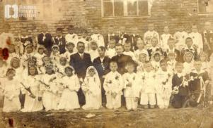 Pamiątkowe zdjęcie z okazji pierwszej komunii świętej wykonane na tle Szkoły Podstawowej w Bronowicach Małych
